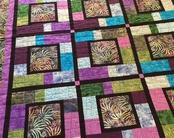 Beautiful batik lap quilt in purples and greens.