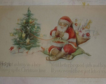 Santa Claus Decorating Christmas Tree With Bag of Toys Antique Pink of Perfection Postcard