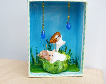 Box decorative baby Sue doll and snail on a cabbage