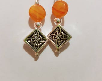 Silver drop earring with orange glass stone and Celtic knot