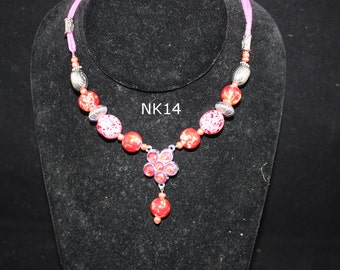 pink leather necklace; pink glass bead necklace; pink rhinestone necklace; silver metal bead necklace; pink leather, bead and rhinestones