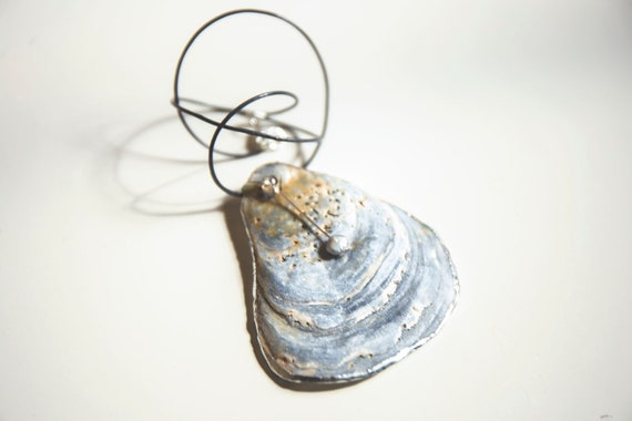 Soldered oyster shell with freshwater pearl on dark grey leather rope choker.