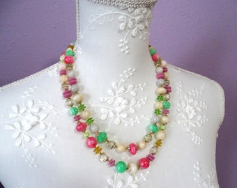 Beaded necklace marked made in Japan. Lovely springtime colored beads with gold tone caps.