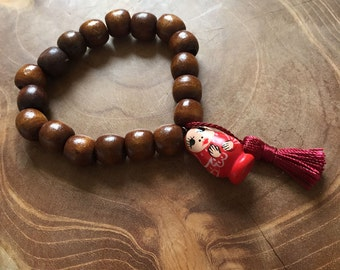 Sweet Red: an elastic beaded bracelet with brown wooden beads, dark red silk tassel and red handpainted matryoshka - last one!