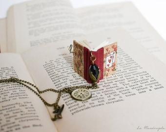 """Collana con il libro rosso  """"Alice nel paese delle meraviglie"""". Libro in miniatura con carte e rose disegnate e citazione del romanzo."""
