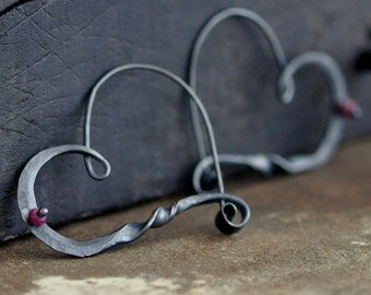 dark twisted heart, a hand wrought  heart hoop in sterling silver with a ruby bead and a dark patina.