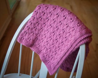 Hand knit pink baby blanket with intricate pattern