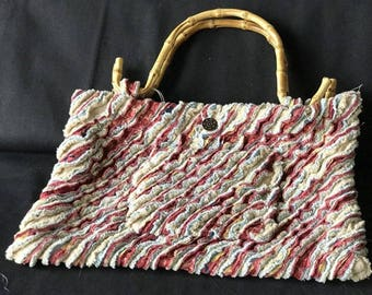 red, tan clutch purse with bamboo handles, outside pocket, multi layered fabric