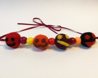 Needle felted necklace of four smiley faces in autumn tones with coloured wooden spacer beads strung on an 80cm burgundy 2mm satin ribbon