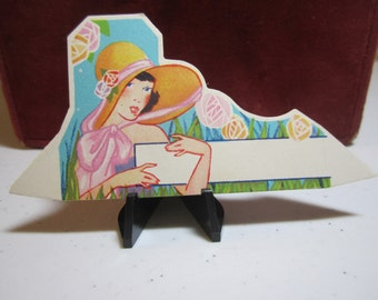 Colorful art deco 1930's unused die cut place card pretty lady in 1930's era hat in garden with stylized deco flowers