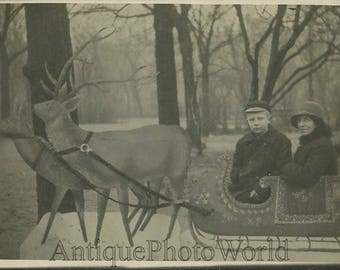 Boy with mother in fake deer sled antique photo