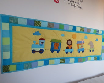 Blue and yellow quilted kid's wall hanging with animals and trains