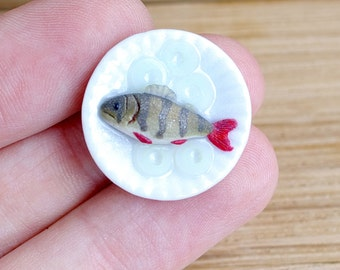 Miniature, realistic fish river perch on a plate. For dollhouse in 1:12 scale