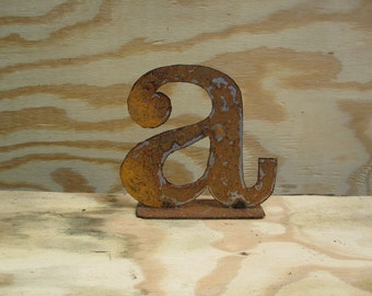 "Lowercase metal letter ""a"" on stand"