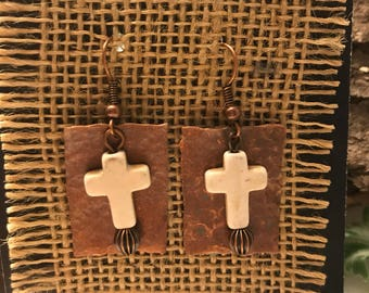 Copper colored textured metal disks complimented by ivory crosses