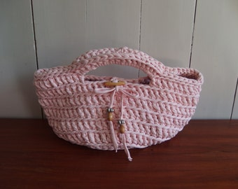Crochet t-shirt yarn basket in the color light pink . Finished with wooden and silver beads