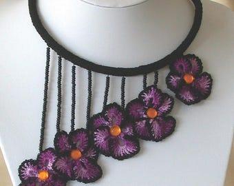 Crocheted purple pansy set on a black crochet black choker
