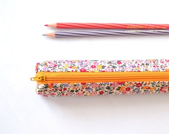 Small pencil case/zipper pouch with small flowers and leaves in red, purple, pink and yellow on a white background, with a yellow zip