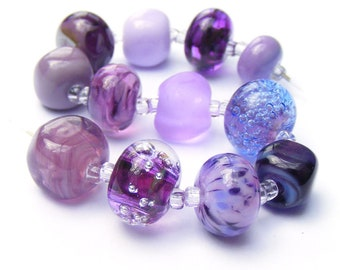 Handmade lampwork glass bead set of 12 mainly purple renegade lampwork orphans
