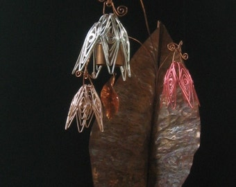 Softly chiming garden bell in a bouquet of copper flowers and leaf atop a stake for planting in garden or houseplant.
