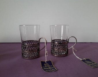 Two glasss beakers with silver plated cradles