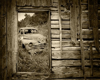 Rusted Abandoned Car viewed through the Window of a Weathered Wall in Ontario Canada showing the Ravages of Time A Sepia Toned Photograph
