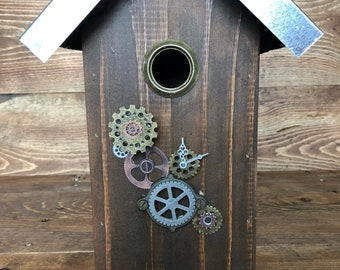 Steam punk outdoor birdhouse with metal roof and gears.