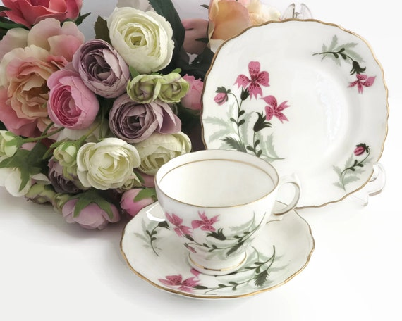 Colclough trio, cup, saucer, and plate with pattern of pink lilies and green leaves, footed cup, gilt trim, England, mid 20th century