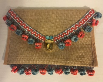 Exotic straw clutch or bag with chain with red and blue Pom Pom decoration