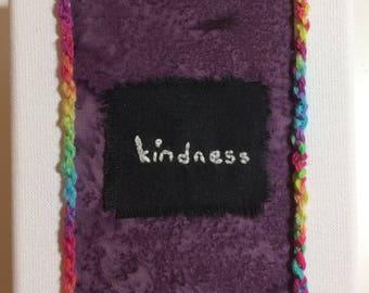 Textile word art - kindness; colourful batik, embroidery and rainbow braiding