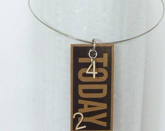 Pendant tag made from cardboard and wooden figures. Upcycling