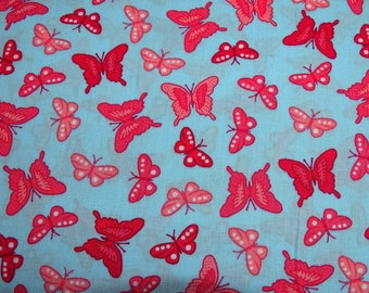 Printed cotton fabric red and pink butterflies on blue background patterns