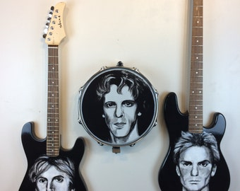 The Police. Recycled musical instruments with all three members Sting,Andy Sommers and Stuart Copeland painted on their own instruments