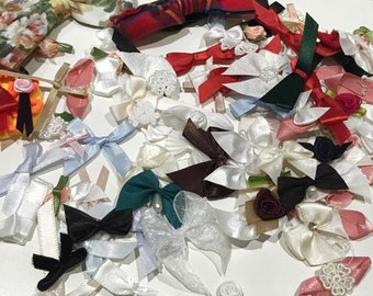 Pack of 100 assorted ribbon bows, pearls, ribbon roses etc.