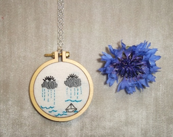 Embroidered necklace of crying clouds and paper boat