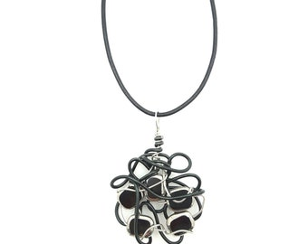 Black and silver necklace that can be worn as a pendant on a strip of leather or at the neck on a hoop