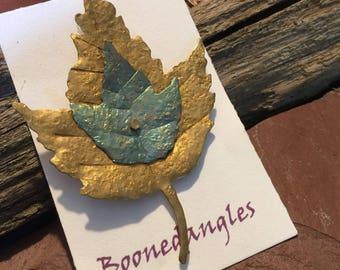 Maple leaf pin. Titanium and brass.