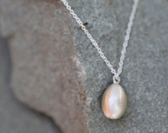 Sterling Silver egg pendant necklace on dainty chain symbolizing the full circle of life