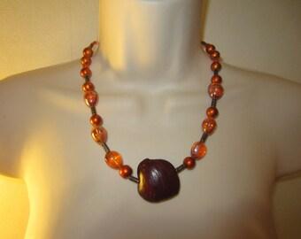 Orange pendant necklace in seed pod of Creeper
