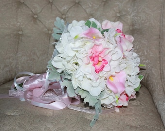 Brides hydrangeas in white with pink calla lilies and orchids. Accented in dusty miller and Euphorbia. Wrapped in triple logn ribbons