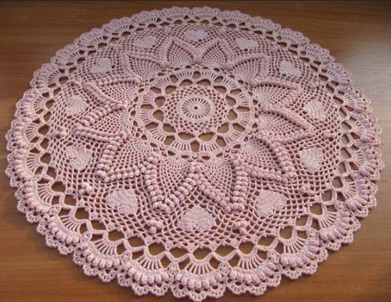 Pink crocheted table topper with pineapple and popcorn stitching