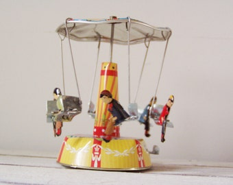Colourful carousel miniature, vintage, tin, merry go round toy with six seated figures, retro carnival ride red yellow blue, early nineties