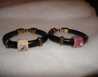 Solid leather bracelets with porcelain center bead and brass-plated pewter sliders