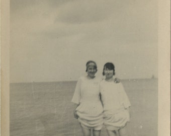 Vintage snapshot photograph of two ladies paddling in sea