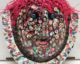 Colorful handmade ceramic mask wall hanging.  Made from white stoneware. This fun mask is Lotsy Dotsy!   Red yarn and bubble paint for hair.