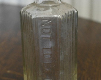 antique clear glass poison bottle