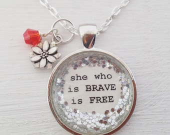 She who is brave is free medium glitter surround pendant necklace with flower charm and ruby red faceted bead dangle