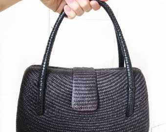 Classic hard shell woven handbag with curved handles.
