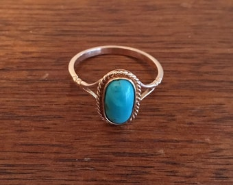 Antique 14 kt yellow gold ring with an Oval Turquoise and split shank with rope border on top size 7 and 1/4