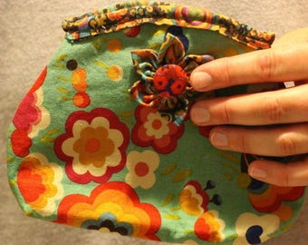 Small, soft fabric clutch with retro floral design